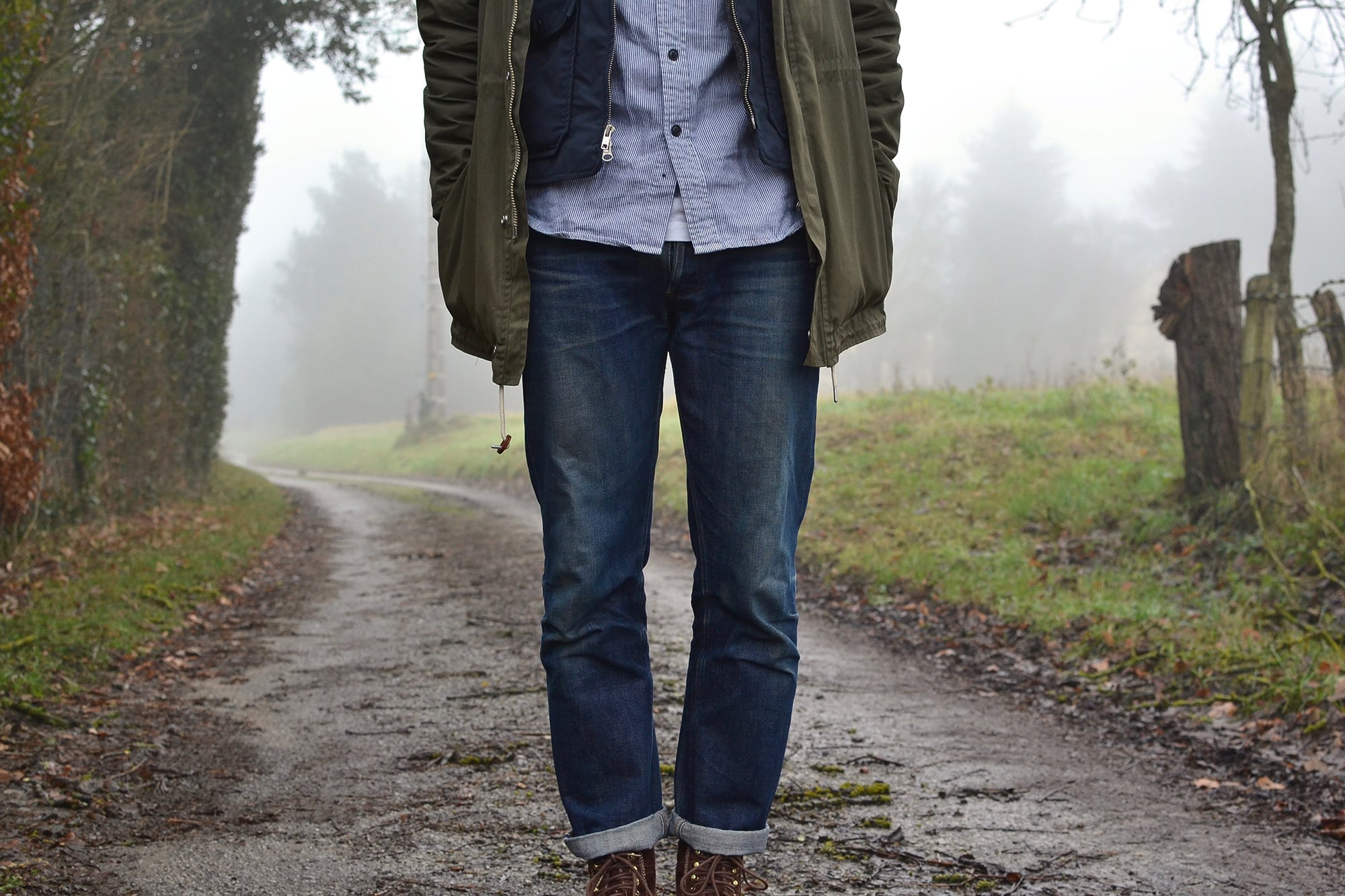 outfit in workwear style with visvim virgil boots , a parka norse projects lindisfarne and engineered garments gilet in tweed and ripstop and a pair of apc new standard butler washed denim