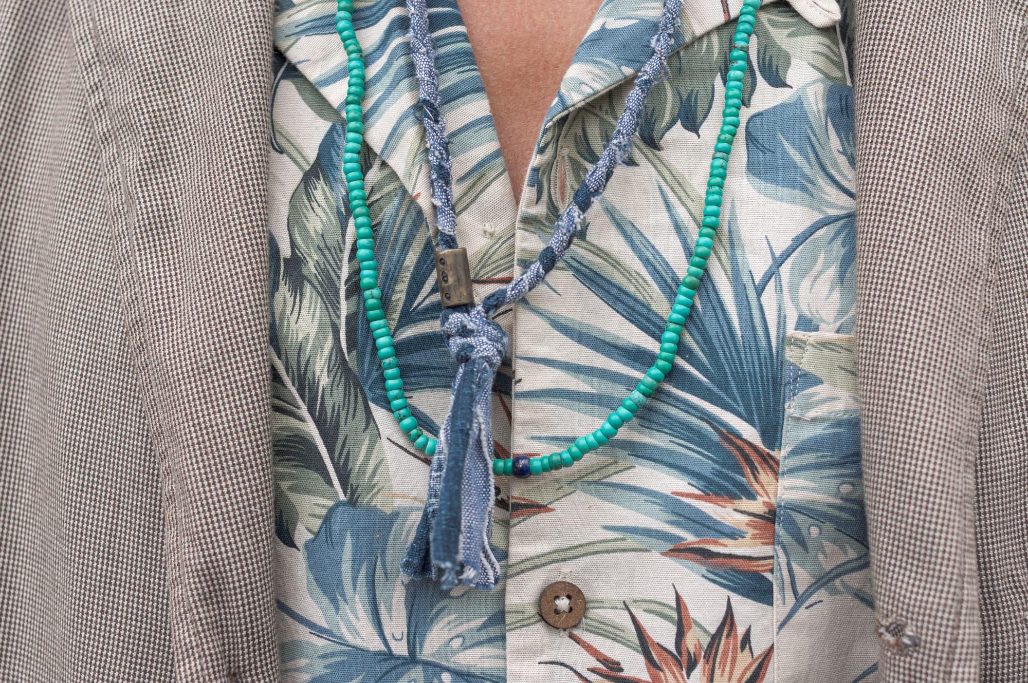 tenue style street heritage workwear d'inspiration militaire avec une veste Engineered Garments Handover loose, une chemise à manche courte à col cubain un jean apc butler et des Visvim FBT et un collier tressé pour homme Borali - lunette atelier particulier et collier blue blue japan