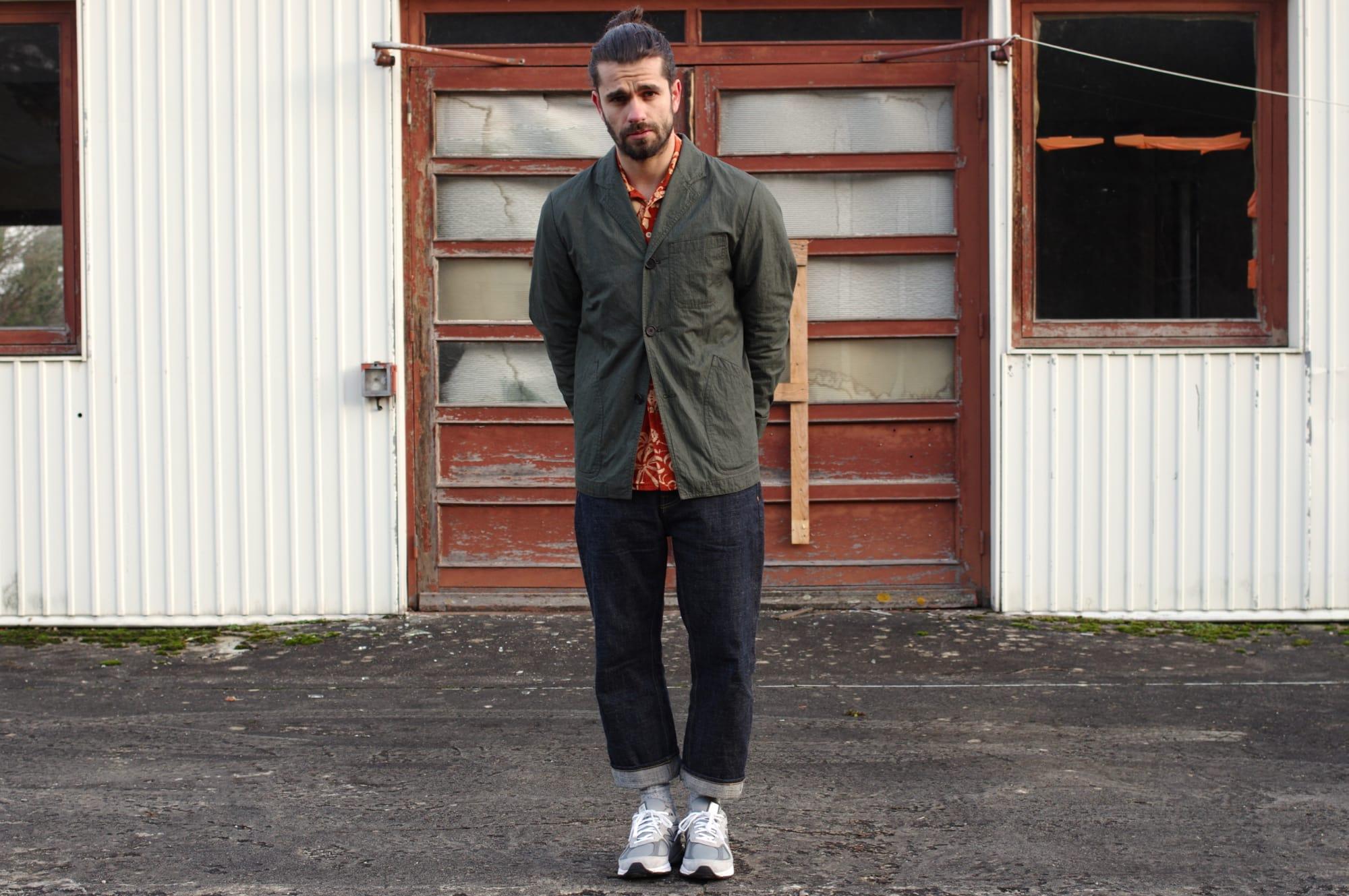 tenue style street heritage workwear avec le stac blazer Kestin Hare, une chemise à fleurs 45rpm, un jean Phi Denim 16oz et des sneakers new balance 990 V4 grise