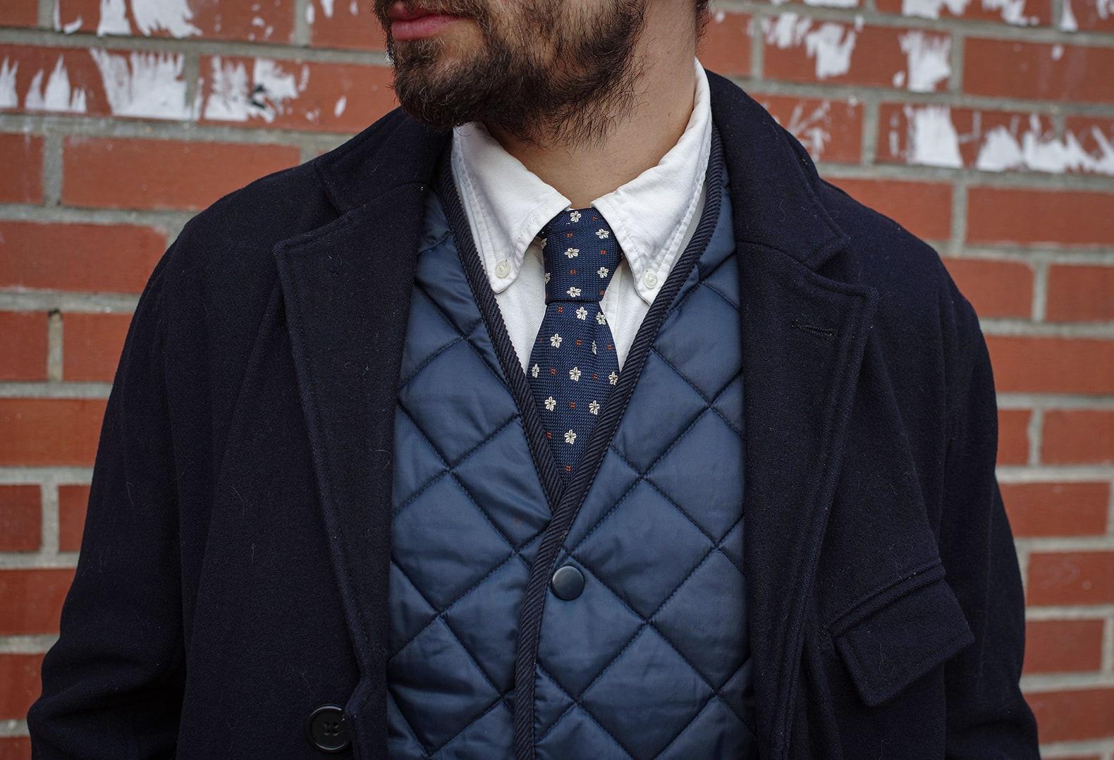layering élégant avec cravate soie motif gilet matelassé type barbour et manteau militaire