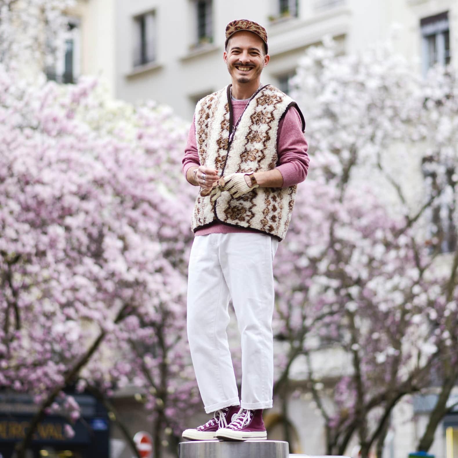 homme en pantalon blanc jean et sweat rose avec un gilet en mouton et des converse violette