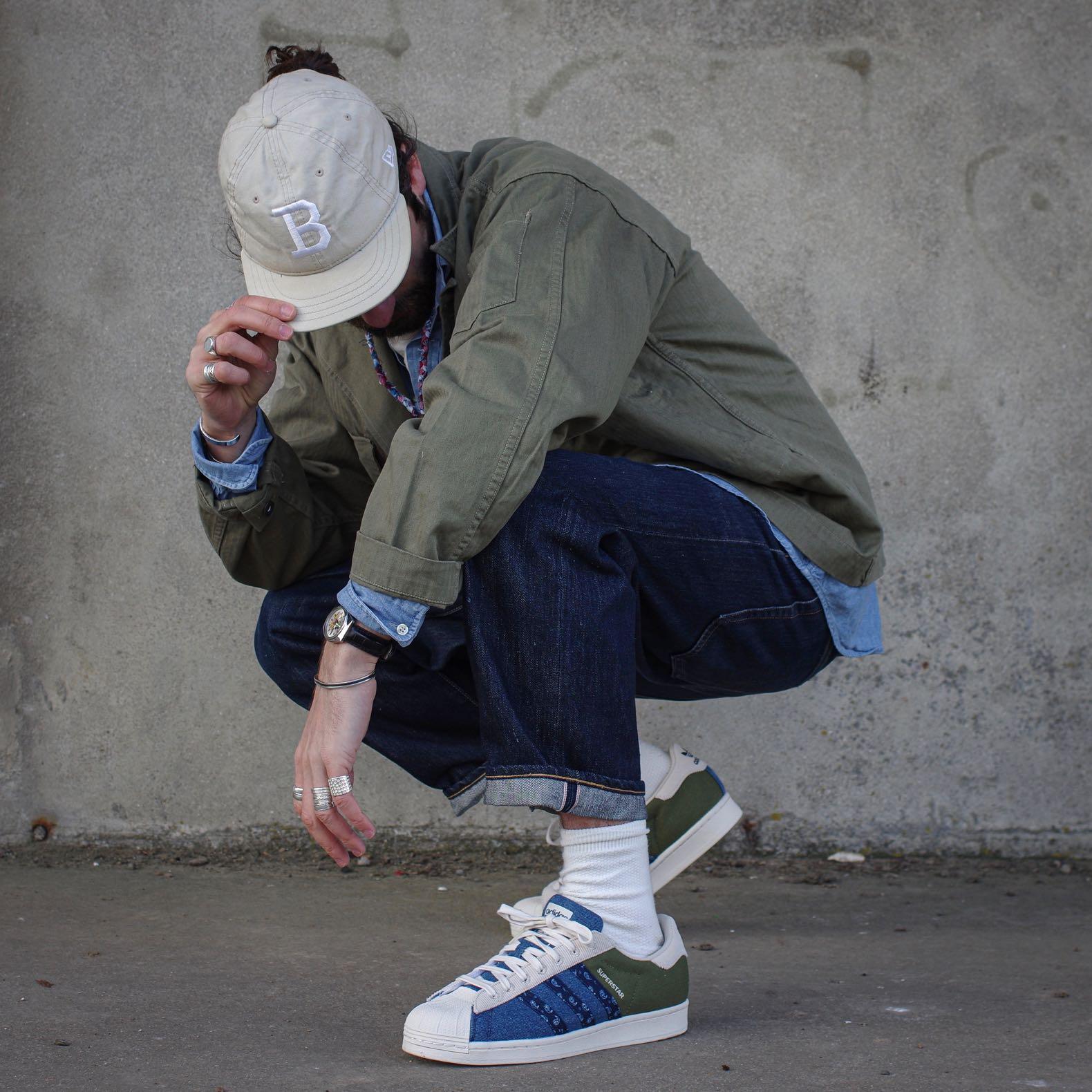 homme dans un style streetweat street heritage avec des adidas superstar patchwork