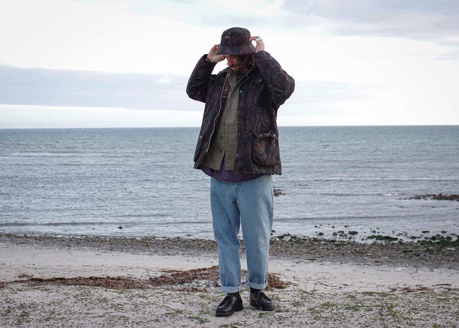 homme en tenue style street heriage avec l'ocean en fond