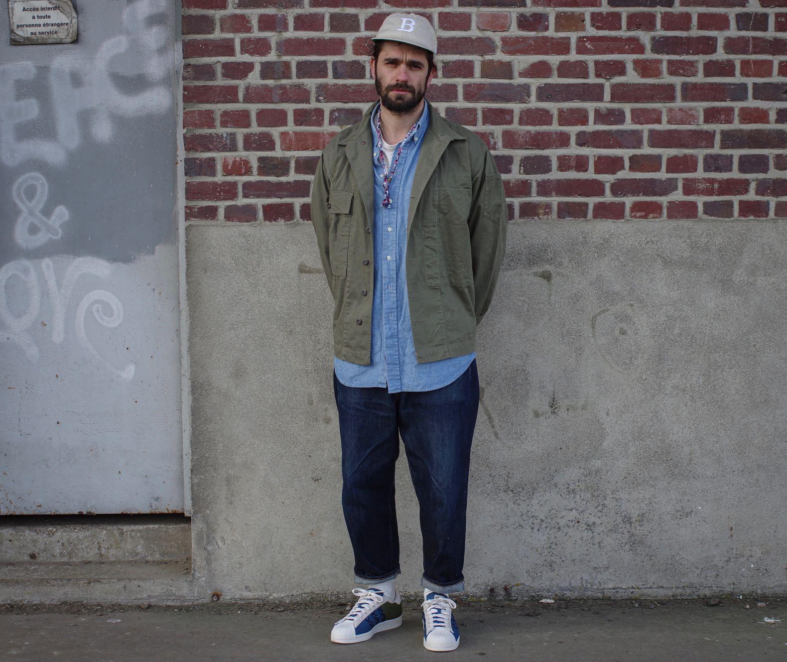 une homme habillé en style streetwear avec une casquette, un jean large et une chemise militaire verte
