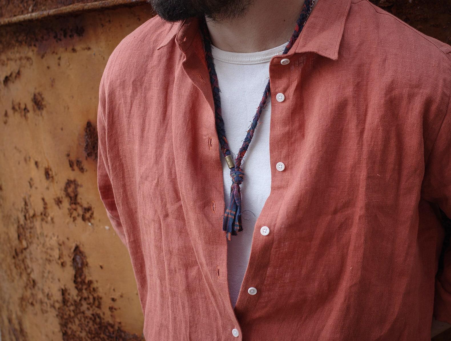 chemise en lin de couleur rouille avec un collier en tissu tressé