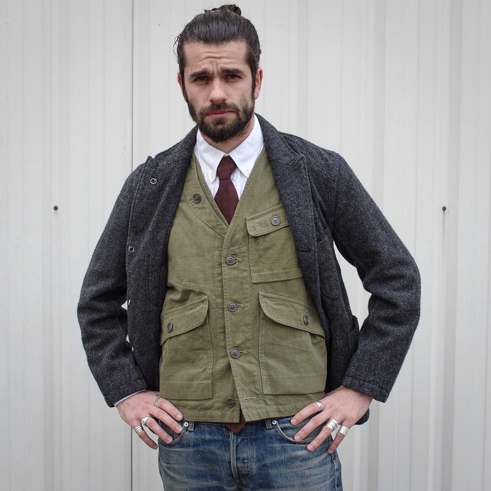 gilet sans manche d'inspiration militaire 1st Pat-rn en coton rep slub, modèle wander vest porté avec une cravate en soie 3 plis Dare in Paris et un blazer en tweed engineered garments bedford jacket