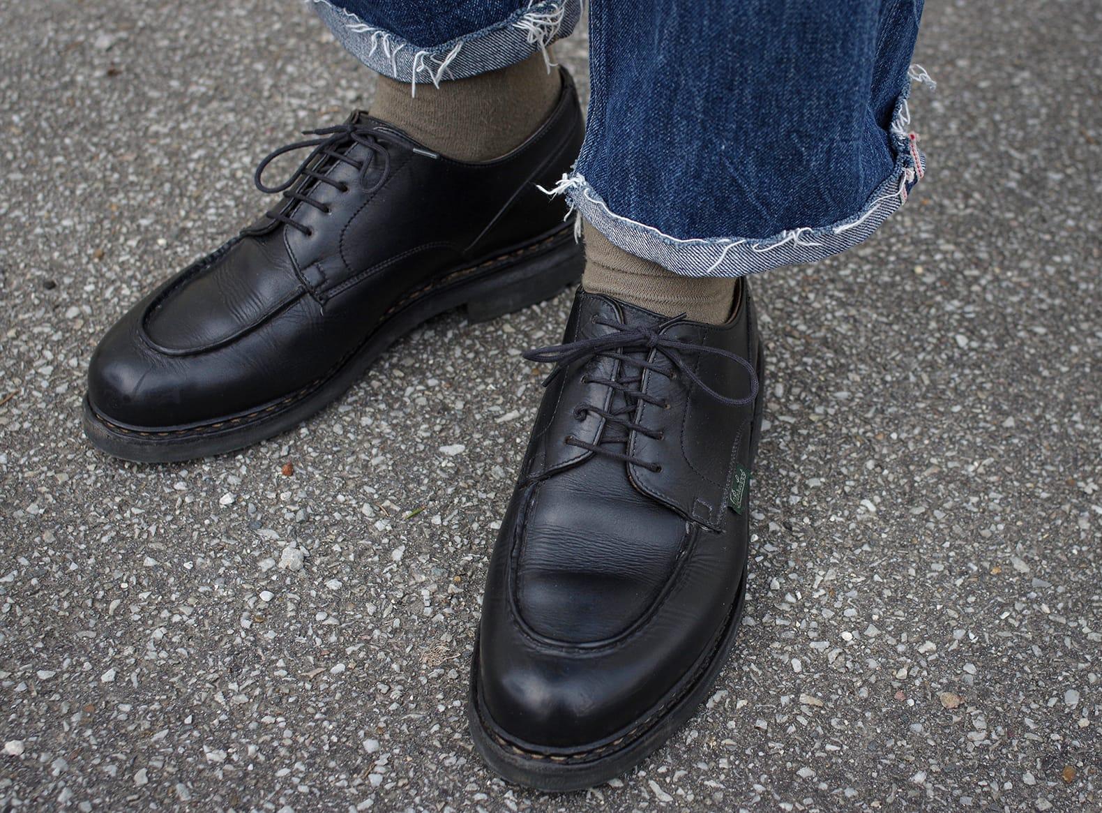 chaussure de la marque française made in France Paraboot et son mythique modèle chambord en couleur noire, portée ici avec un jean coupé bord franc et des chaussettes olive