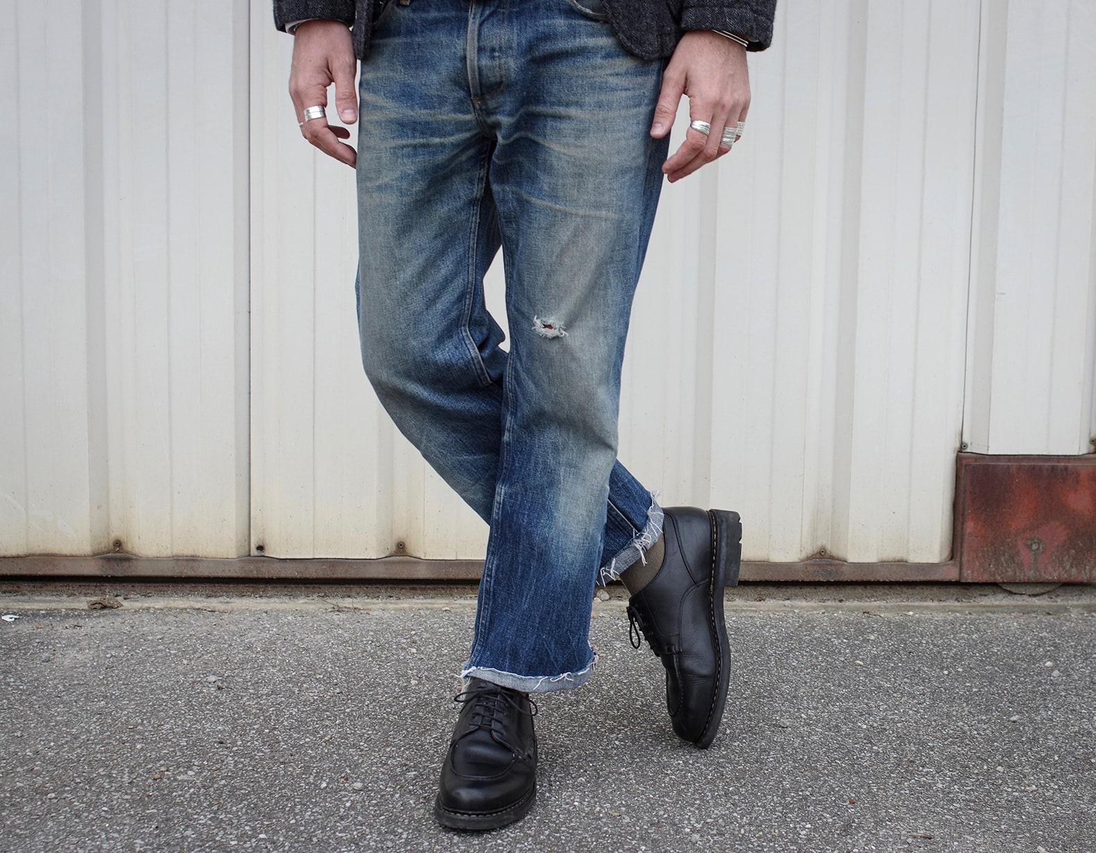 photo d'un jean brut PAC modèle hipster bien patiné et délavé par les années, il est porté avec une paire de paraboot chambord de couleur noire