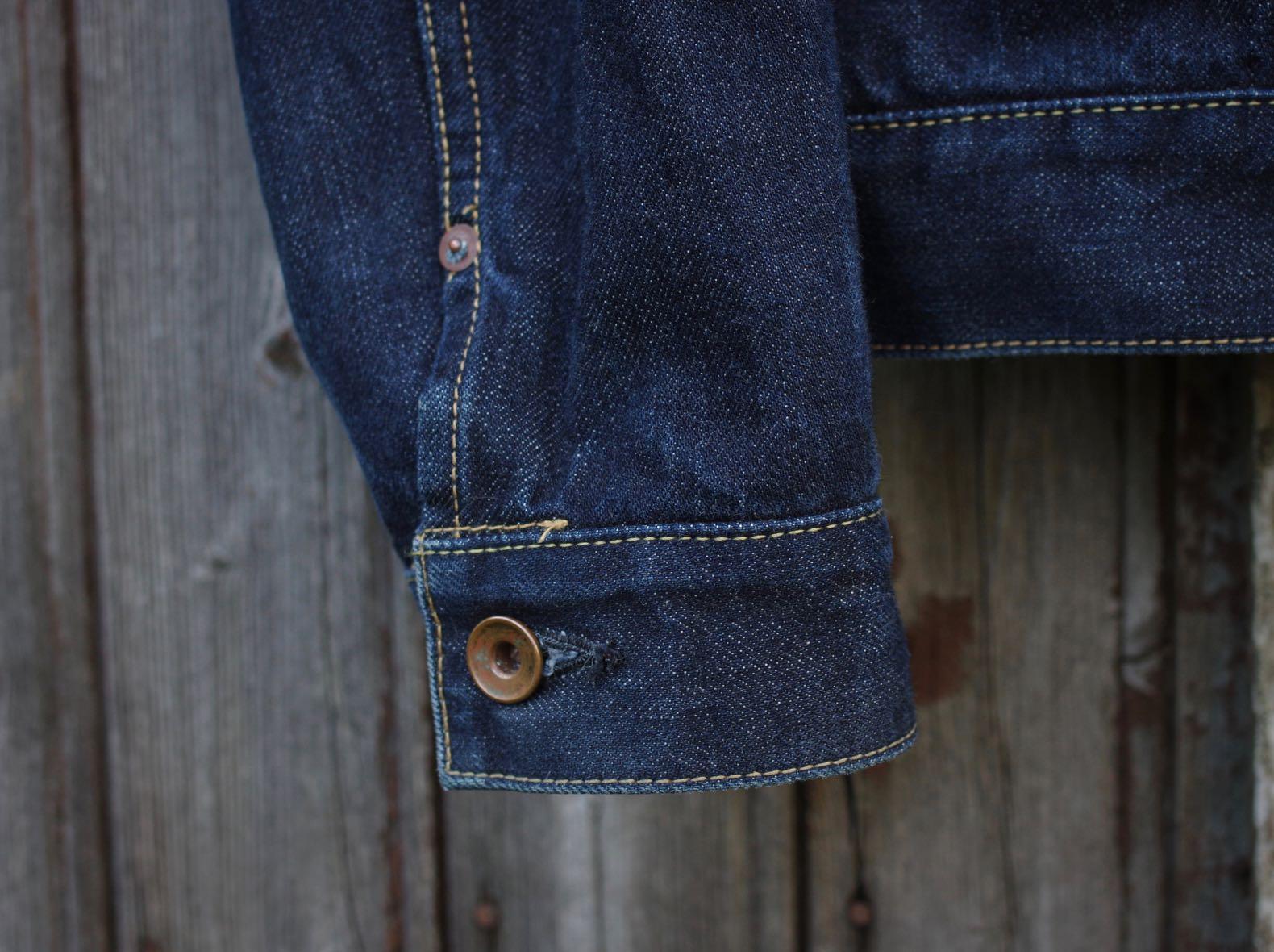 bouton en laiton pour fermer une manche de veste en jean