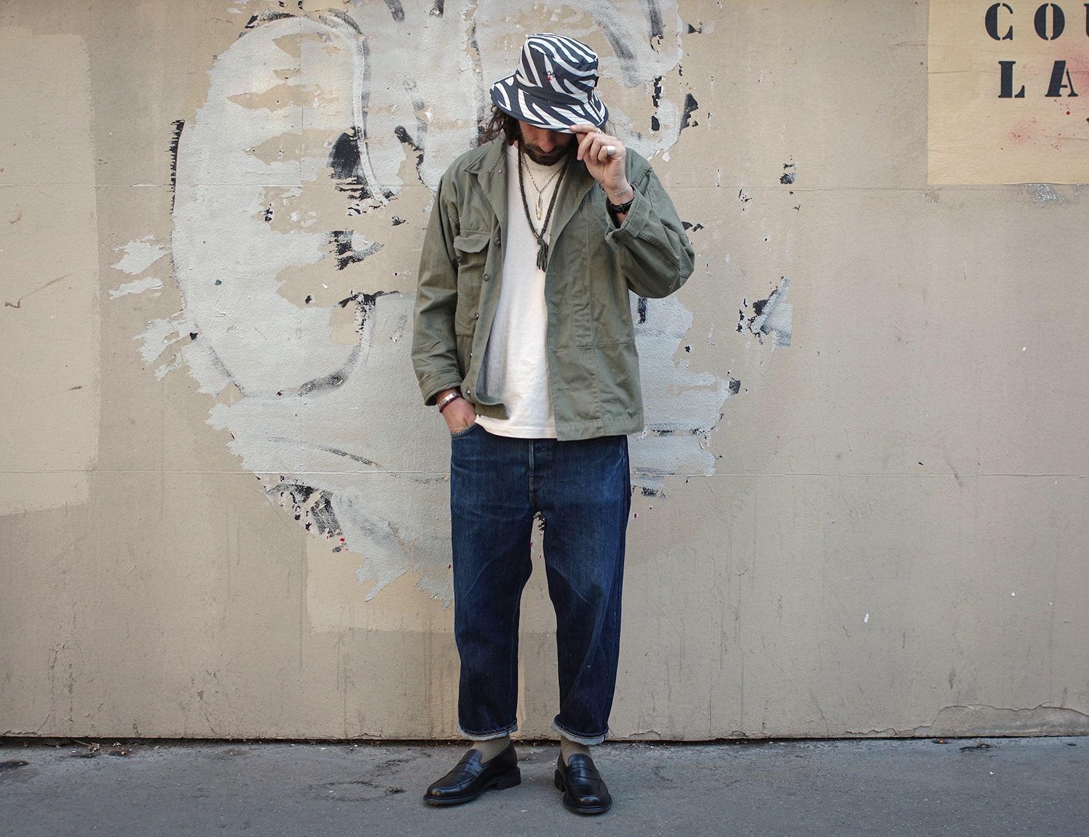 tenue d'un homme style workwear avec une veste militaire arashi denim et un bob zebra barbour et es mocassin noir