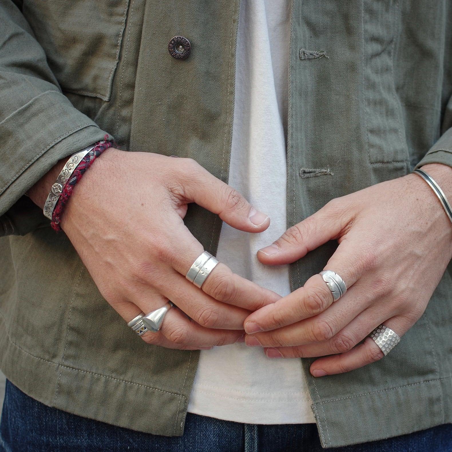 mains d'homme avec des bijoux comme des bagues en argent et bracelets en tissu Borali