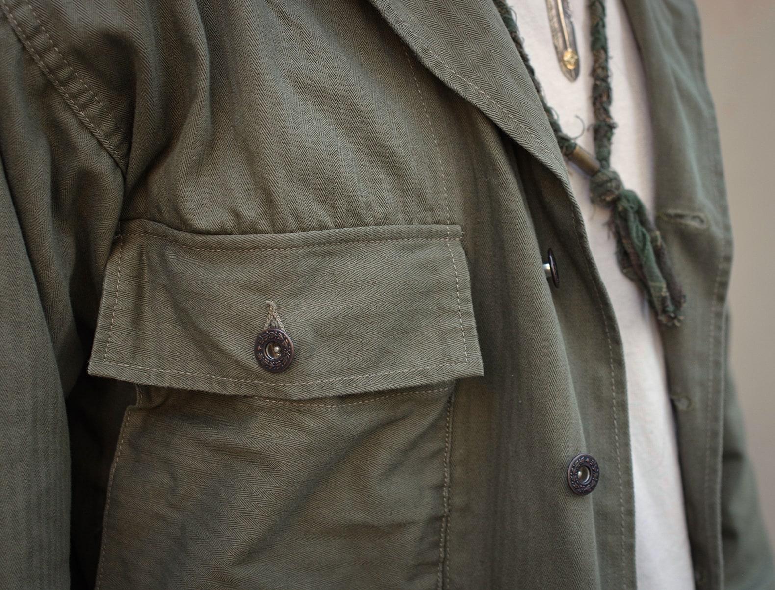 homme qui porte une surchemise militaire vert olive avec un bob zébré barbour x noah