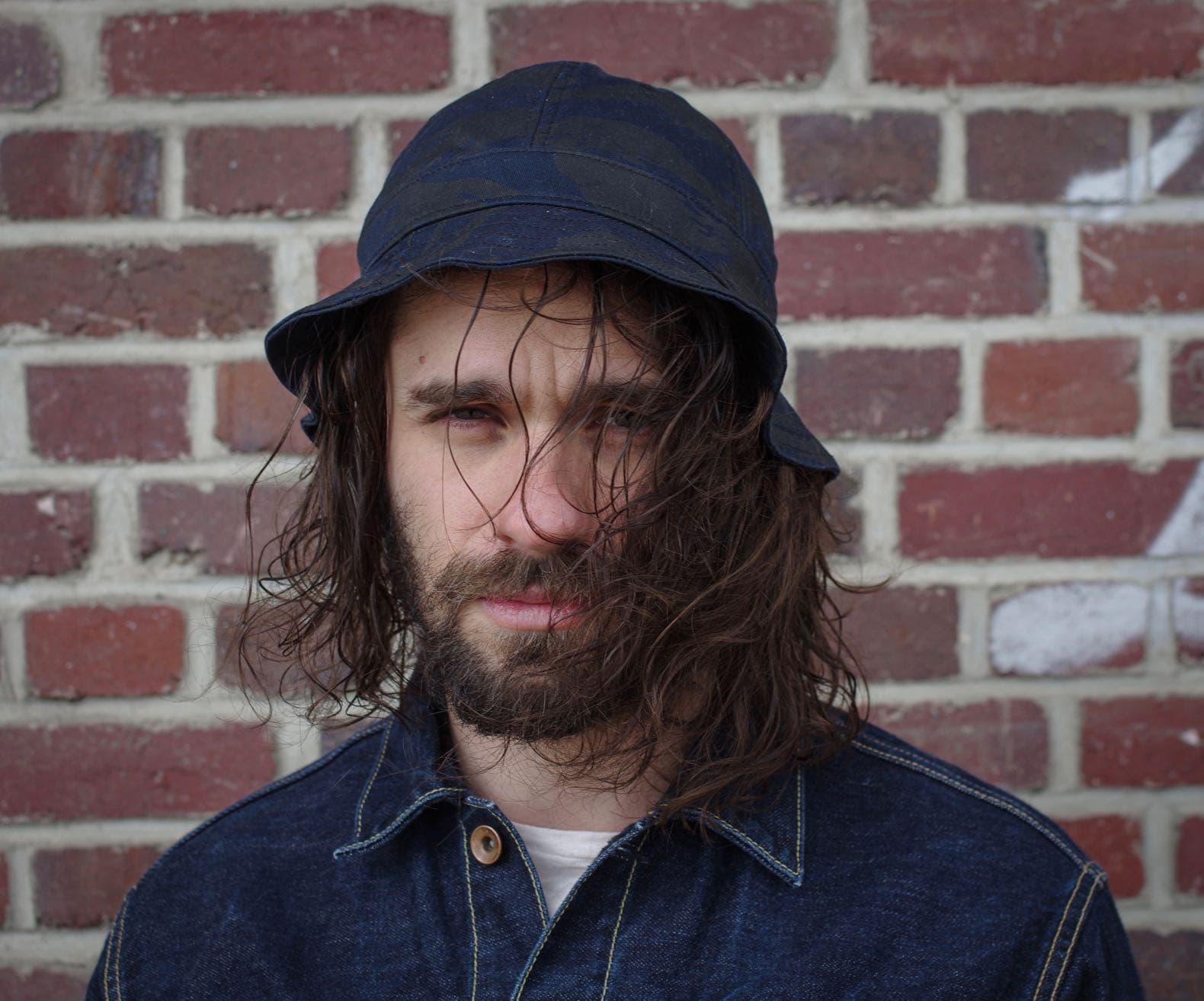 homme avec des cheveux longs détachés et un bob avec un motif camo bleu nuit et ne veste en jean brut phi denim