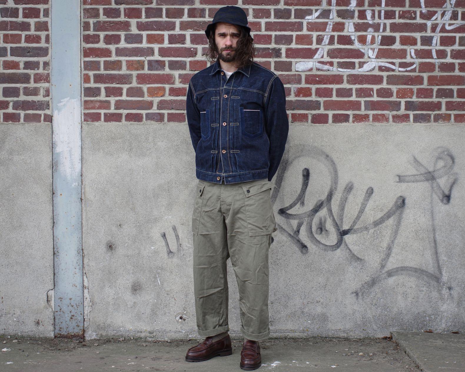 homme à cheveux long habillé avec une veste en jean, un pantalon militaire monkey vert olive et des paraboot reims marron avec un bob
