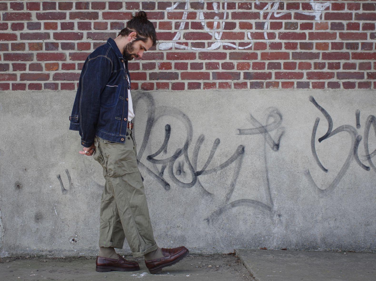 homme qui marche habillé en pantalon cargo militaire et veste en jean phi denim et des mocassins marrons paraboot