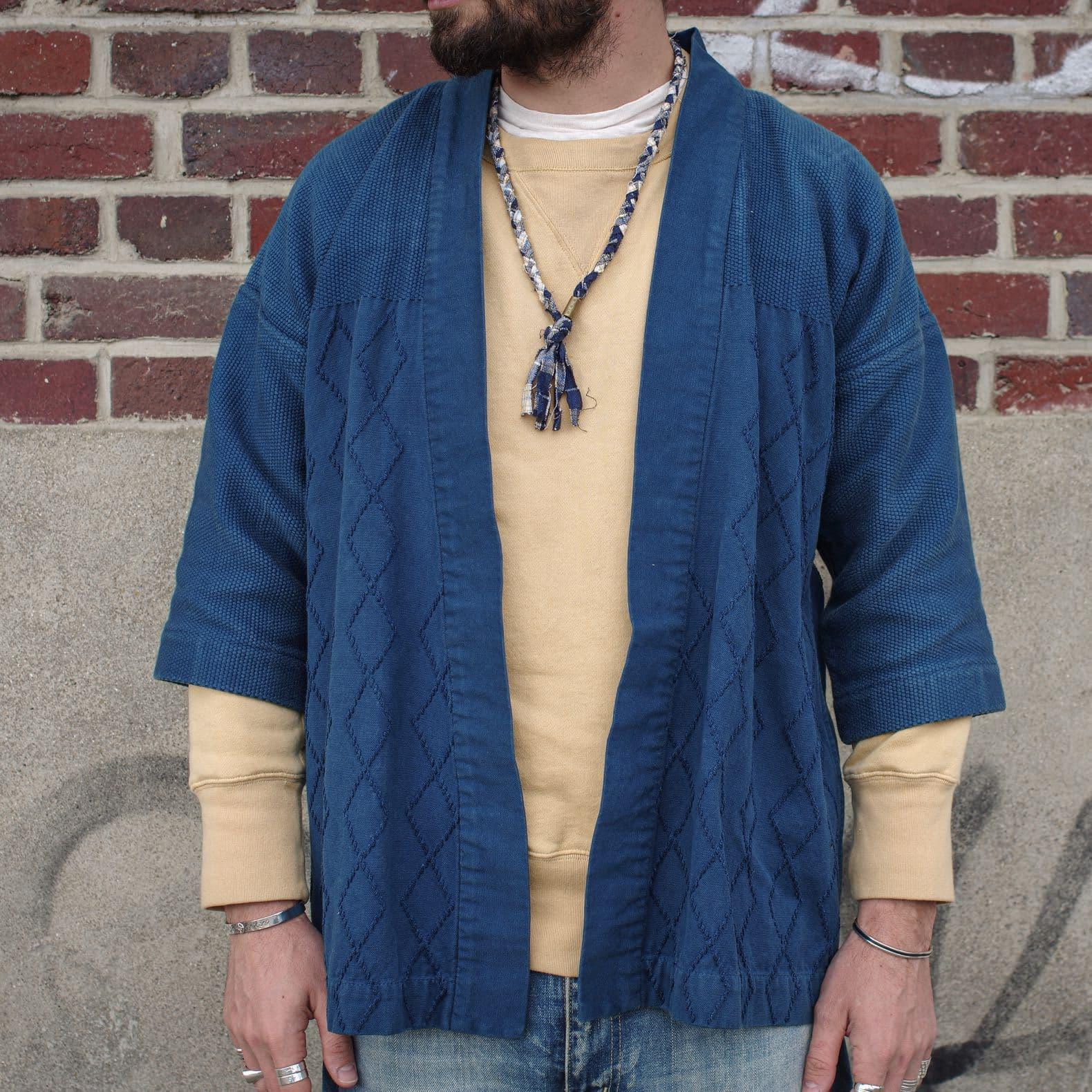 homme qui porte un kimono bleu indigo et un sweat jaune