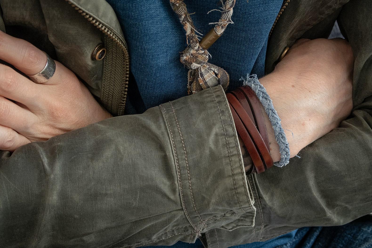 bracelet Borali porté avec un bracelet en cuir sur une veste militaire olive