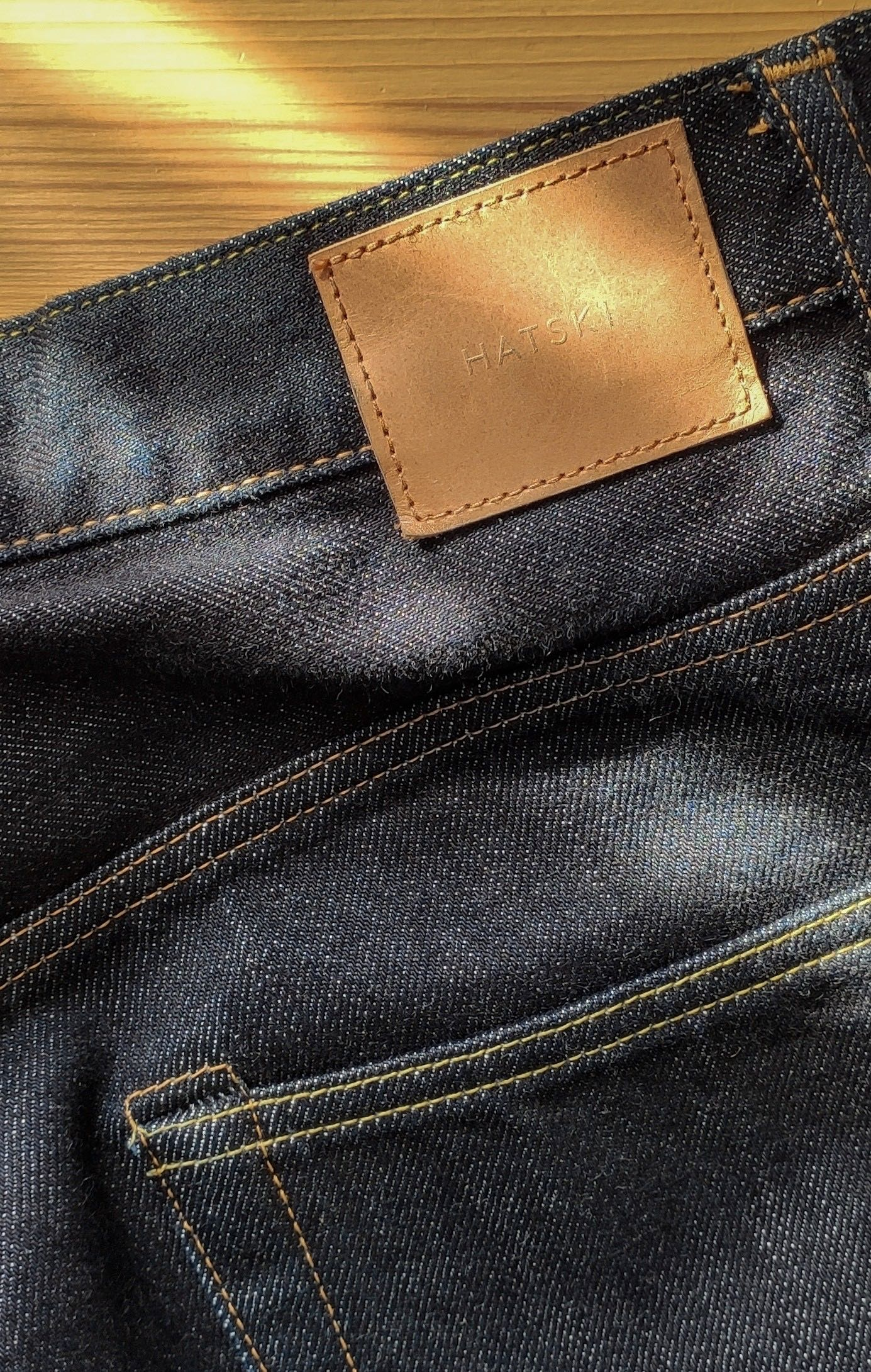 Jean brut loose tapered de la marque Hatski, détail du patch en cuir et de la toile selvedge