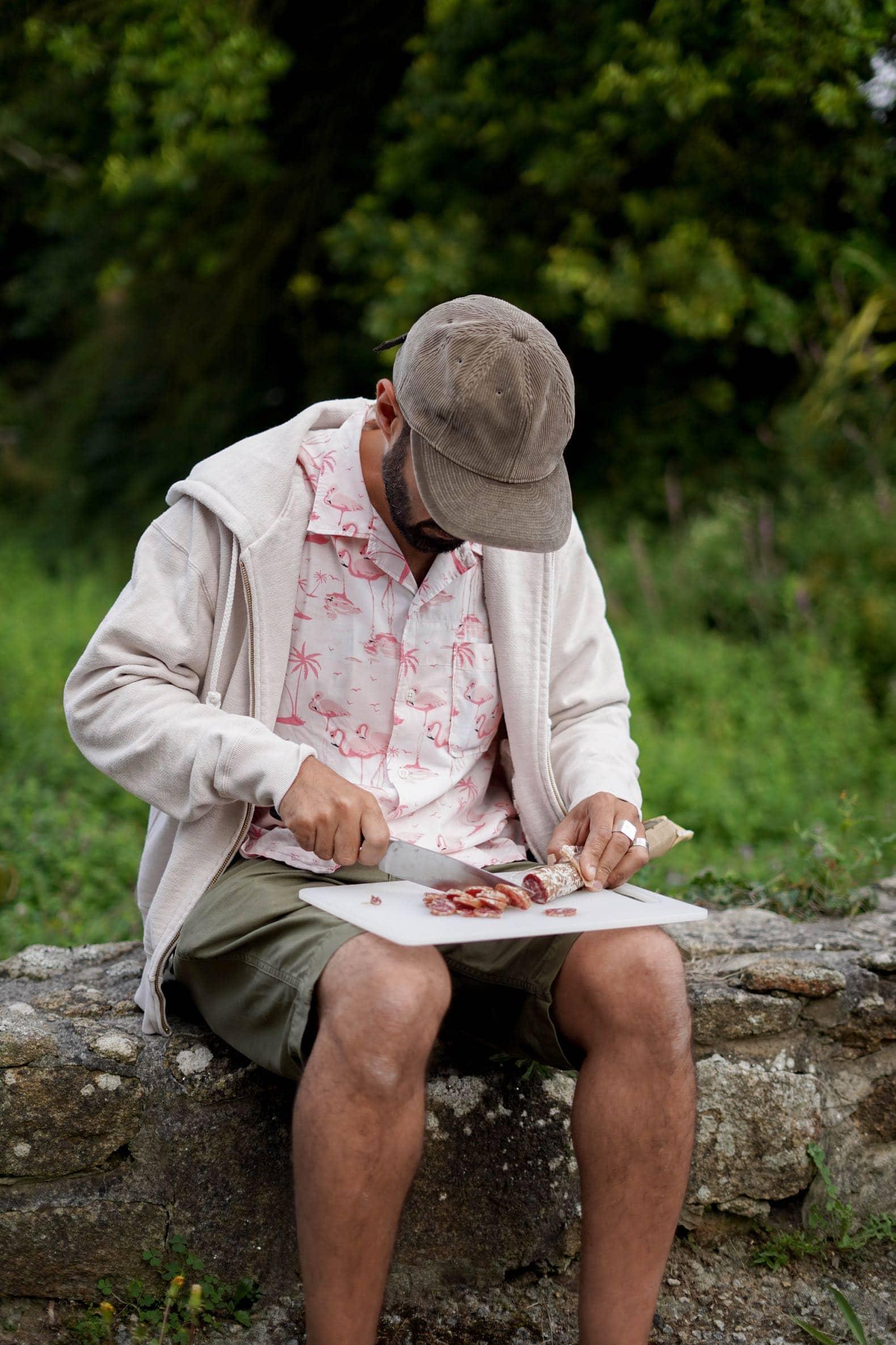 homme couper saucisson